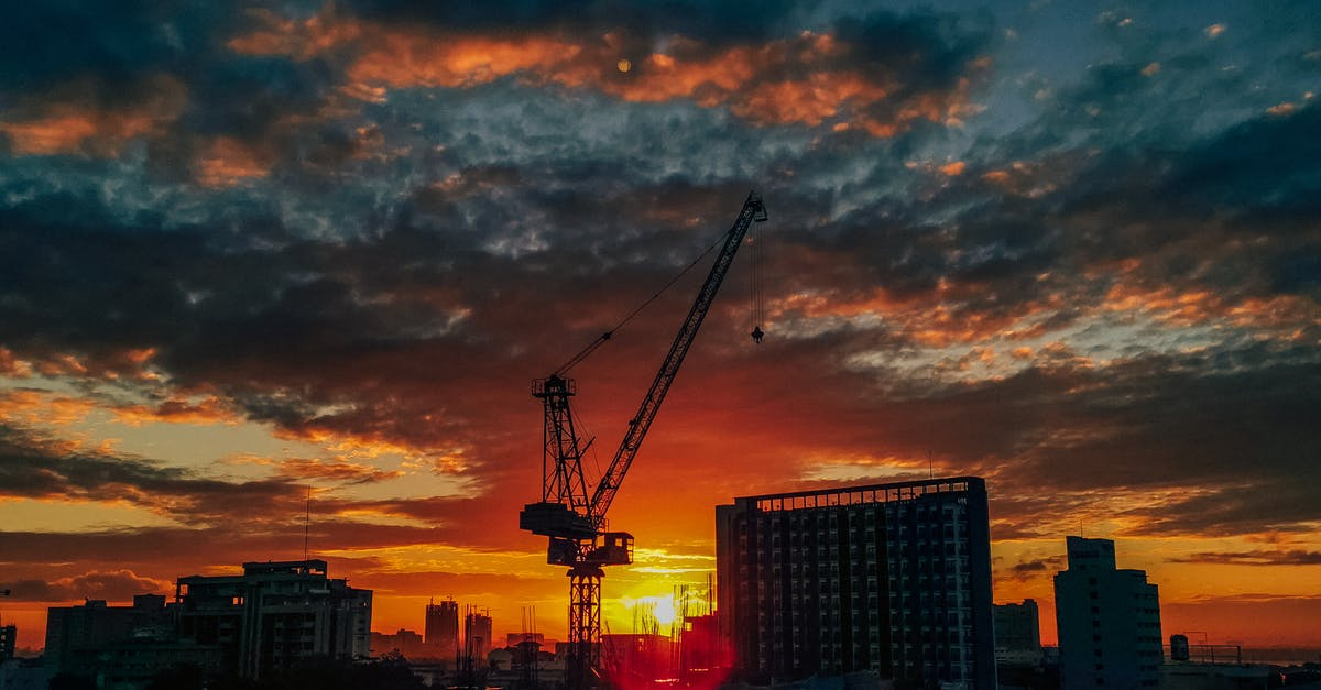 A crane flying over a city at sunset